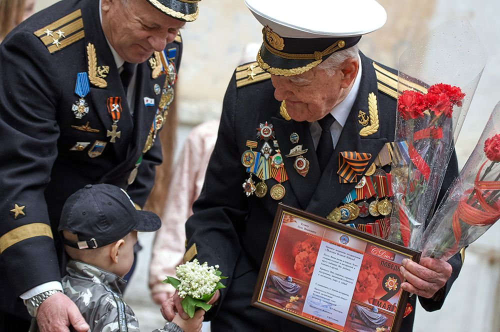 Ветеран Великой Отечественной войны, капитан 1-го ранга Лука Иванович Кузин (справа) принимает поздравления во время персонального парада во дворе своего дома в Севастополе.