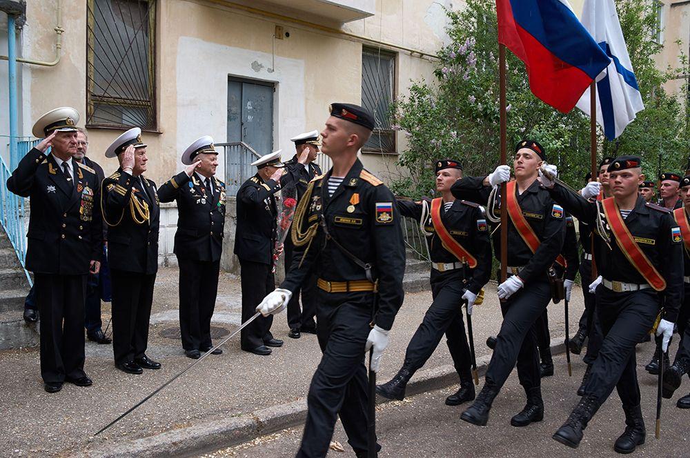 Участники персонального парада для ветерана Великой Отечественной войны, капитана 1-го ранга Луки Ивановича Кузина во дворе его дома в Севастополе.