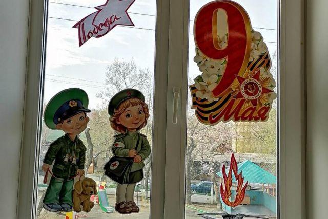 Детские аппликации украсили окна детского сада к празднику.