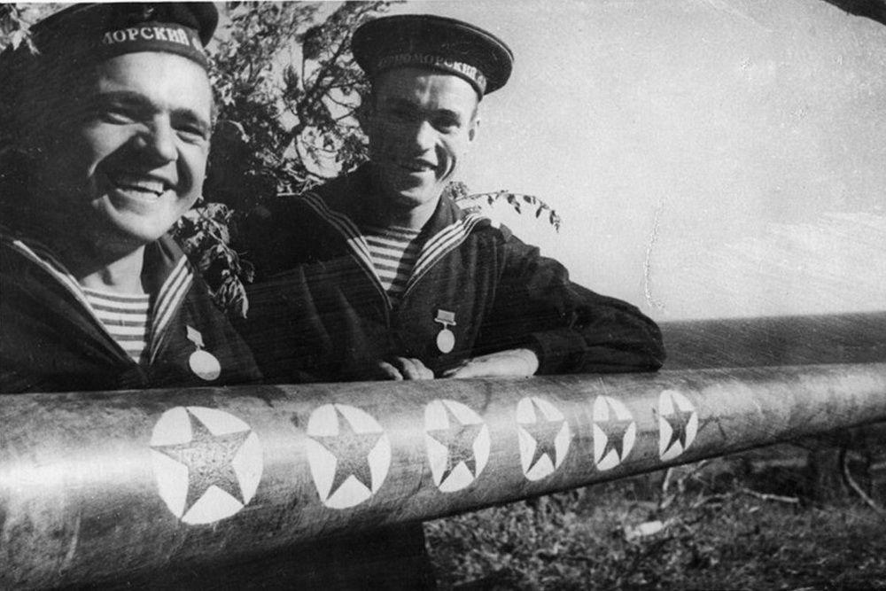 Новороссийские моряки-артиллеристы у ствола орудия с победными отметками.