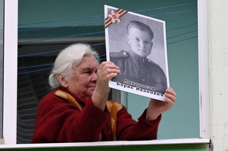 Пожилая женщина на балконе своего дома с портретом ветерана Великой Отечественной войны, Ростов-на-Дону.