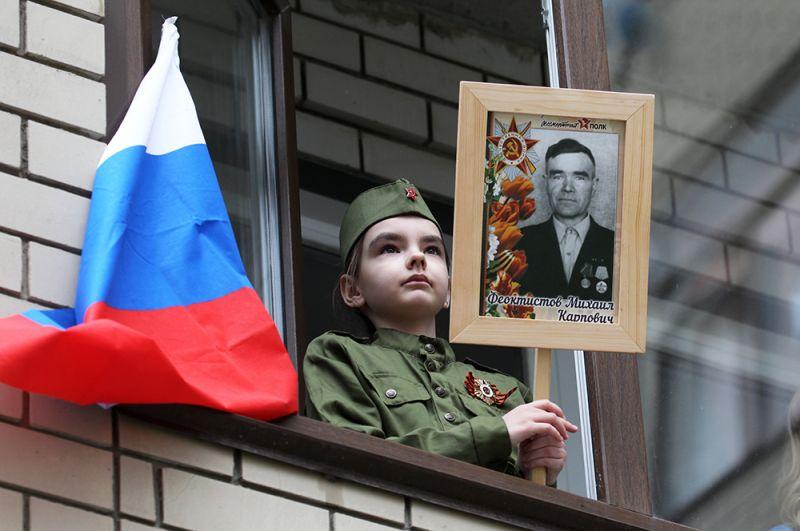 Девочка наблюдает из окна за персональным парадом для ветеранов Великой Отечественной войны, проходящим во дворе жилых домов в Барнауле.