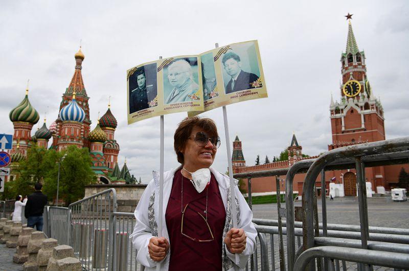 Женщина с портретами участников войны на Красной площади в Москве.