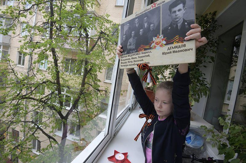 Девочка с портретами своих родственников - ветеранов Великой Отечественной войны, Москва.