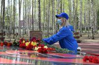 Волонтер возлагает цветы к Вечному огню в Ханты-Мансийске