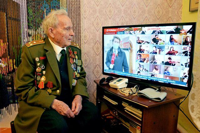 Ветеран Великой Отечественной войны смотрит онлайн-трансляцию акции «Бессмертный полк».