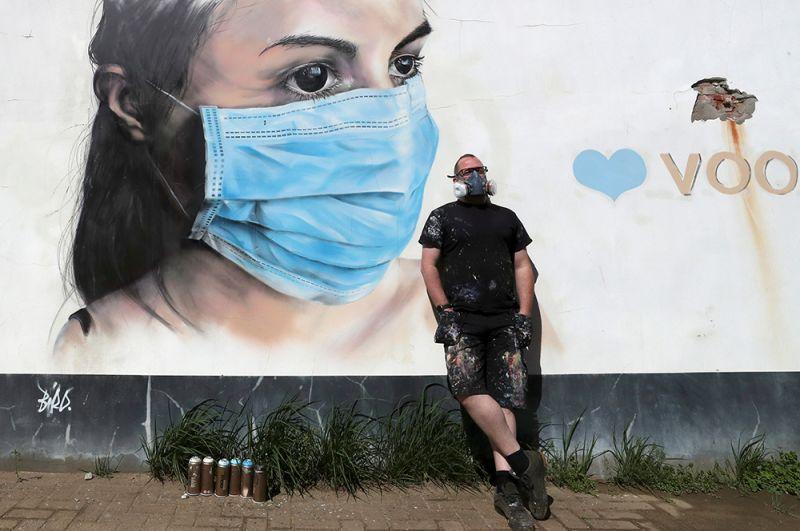 Художник рядом со своей работой в поддержку медиков в Антверпене, Бельгия.