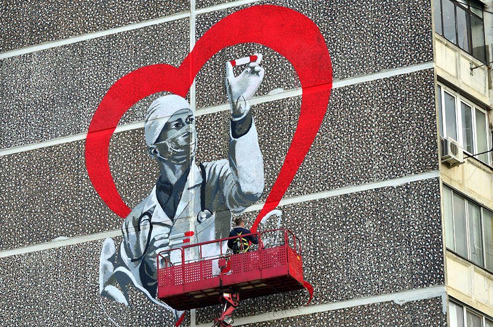 Художник Евгений Аморфис рисует граффити «Спасибо врачам» на стене дома на улице 1 Мая в Краснодаре.