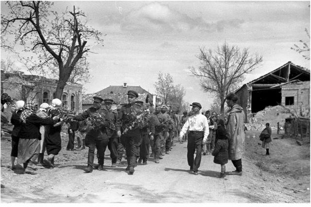В освобожденных территориях советских солдат встречали жители с цветами.