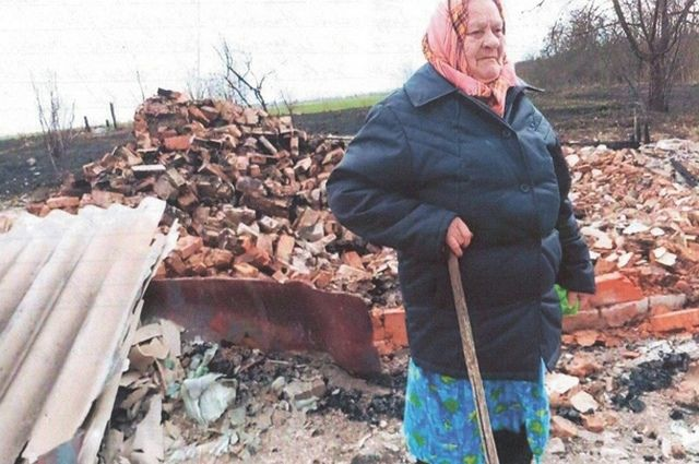 Ефросинья Хомченко возле своего сгоревшего дома, который они с мужем построили в 1970-х годах, а потом ещё долго обустраивали.