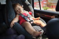 Девочка спит в детском автокресле.
