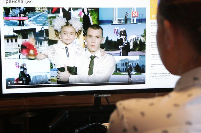 Школьница смотрит трансляцию «Общекрымского последнего звонка».