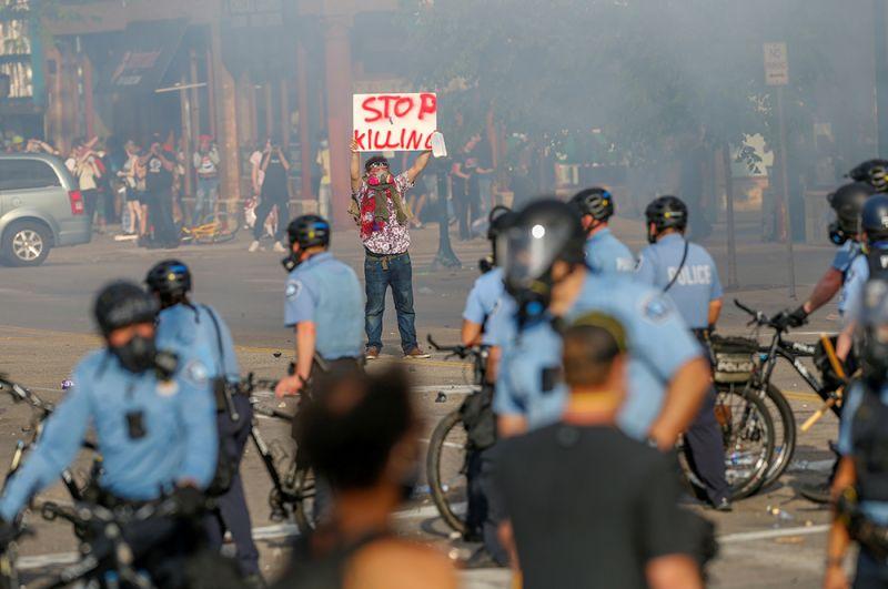 Люди собираются вокруг полицейского участка в Миннеаполисе.