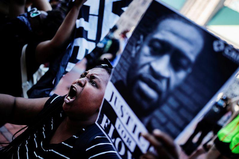 Женщина с фотографией погибшего Джорджа Флойда во время митинга на улицах Миннеаполиса.