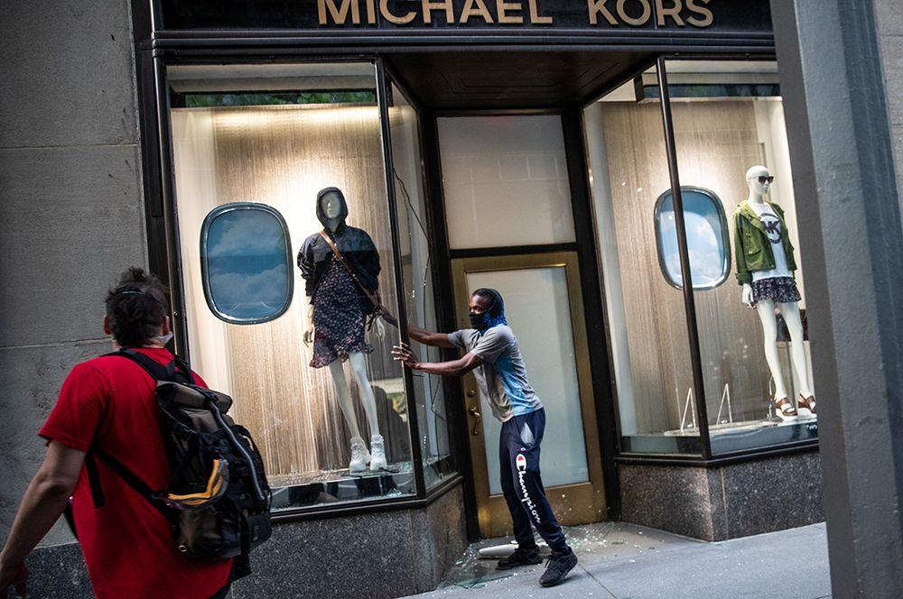 Люди грабят магазин брендовой одежды на Манхэттене в Нью-Йорке.
