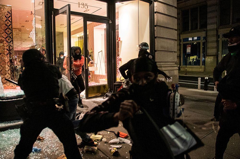 Люди грабят магазин на Манхэттене в Нью-Йорке.