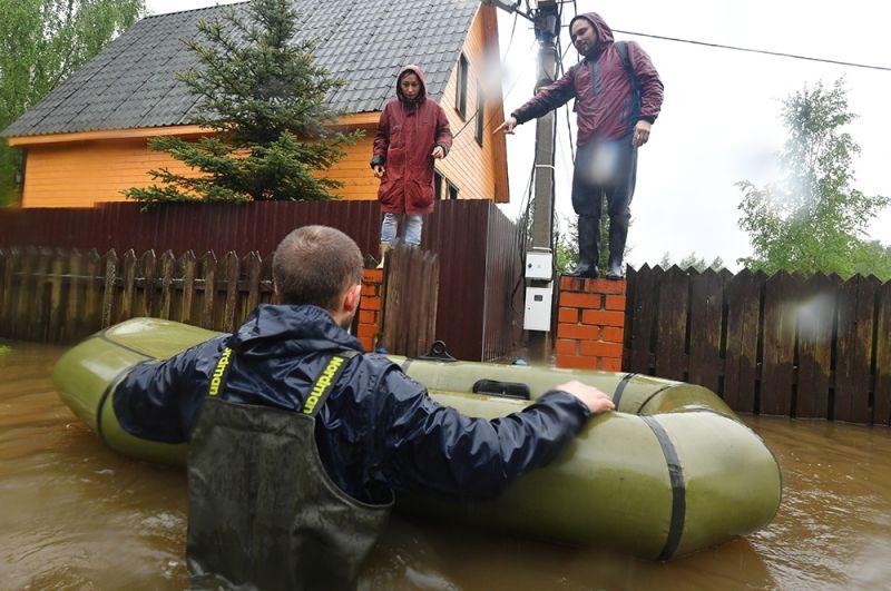 Спасатель эвакуирует жителей дачного поселка, подтопленного из-за разлива реки Воря в Щелковском районе Московской области.