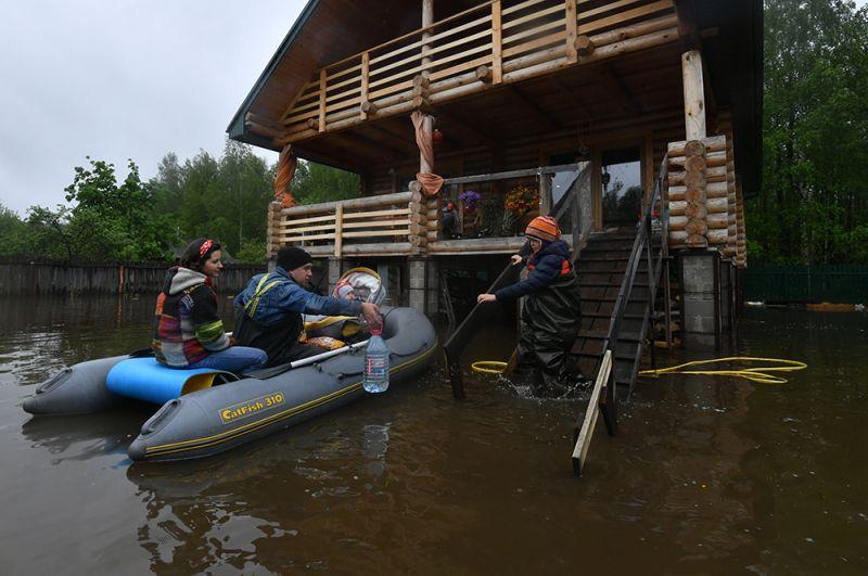 Жители дачного поселка на лодке возле своего дома, подтопленного из-за разлива реки Воря в Щелковском районе Московской области.