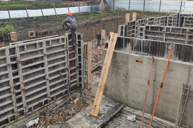 На месте стройки уже вырыт котлован, возводится фундамент и арматура для несущих стен.