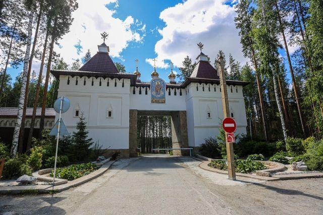 Шлагбаум перед воротами Среднеуральского монастыря закрыт.