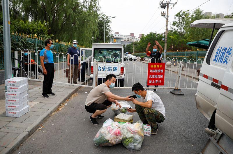 Образцы коронавируса, найденные на оптовом рынке Пекина «Синьфади», оказались старше распространённых в Европе штаммов. На фото: доставка еды жителям жилого комплекса, который находится на карантине.
