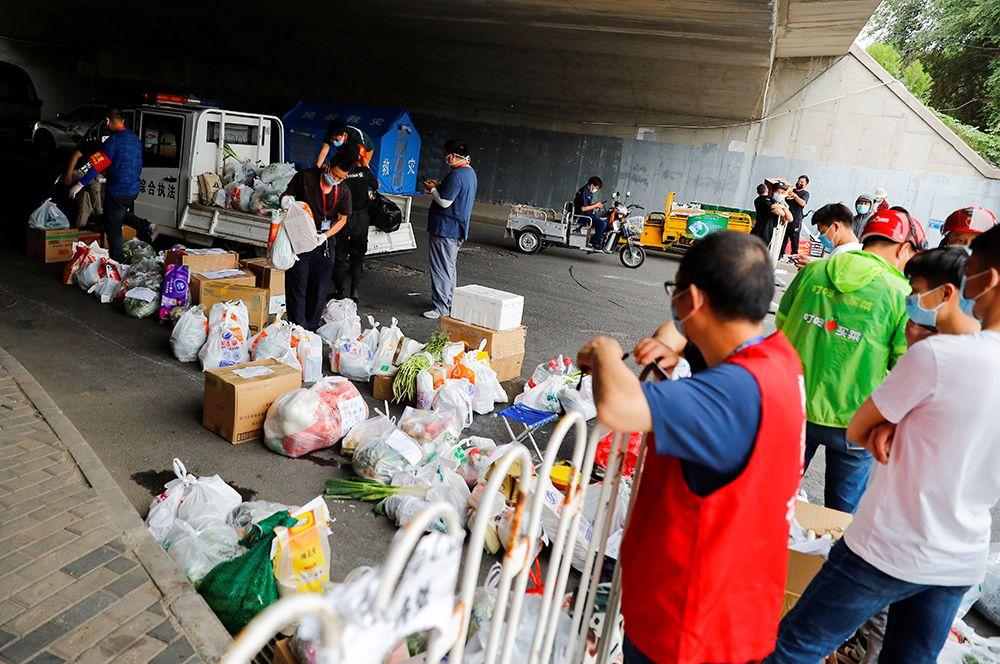 По словам эпидемиолога Лю Цзюня, отследить точный путь попадания этого коронавируса на рынок в Пекине довольно сложно. Так, например, он мог находиться в партии замороженных продуктов и вместе с ней прибыть из-за рубежа. На фото: доставка еды жителям жилого комплекса, который находится на карантине.