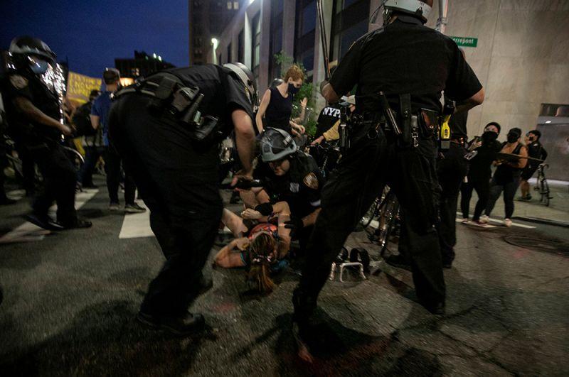 Сотрудники правоохранительных органов задерживают женщину во время акции протеста в Бруклине, Нью-Йорк.
