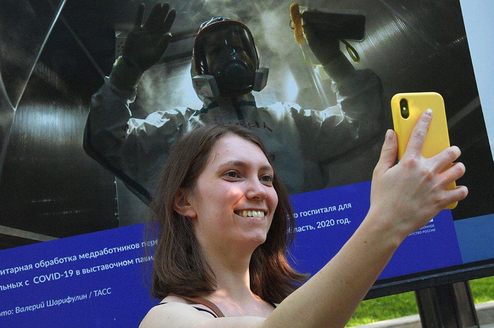Девушка фотографируется на фоне экспозиции, посвященной работе врачей и медицинского персонала.