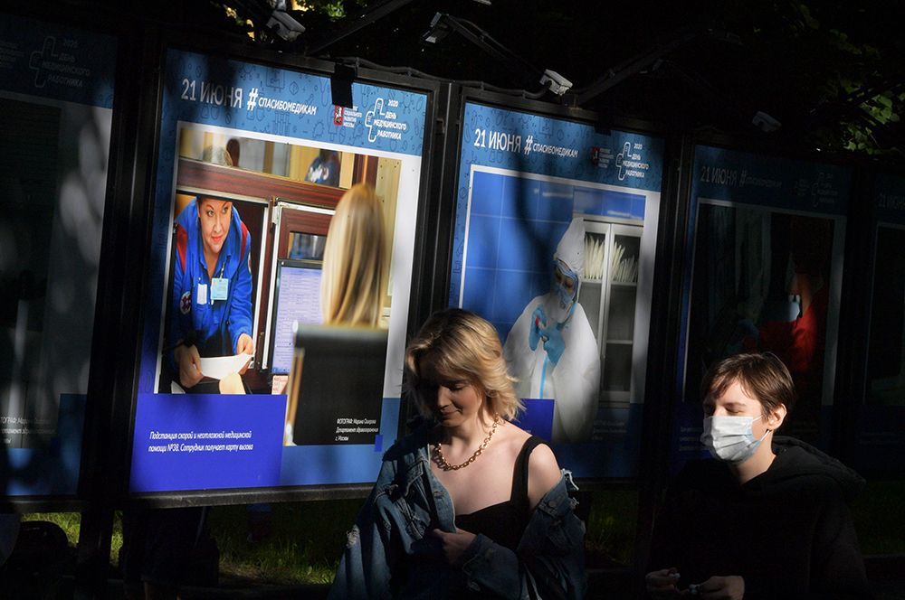 Прохожие идут мимо экспозиции, посвященной работе врачей и медицинского персонала.