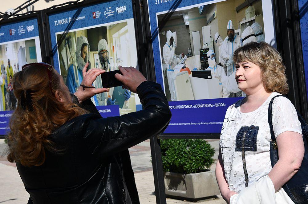 Прохожие фотографируются на фоне экспозиции, посвященной работе врачей и медицинского персонала.