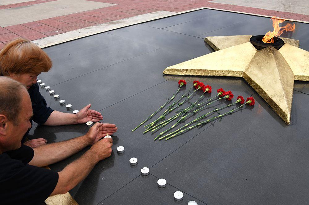 Люди зажигают «свечи памяти» у Вечного огня Мемориала боевой и трудовой славы забайкальцев в Чите.