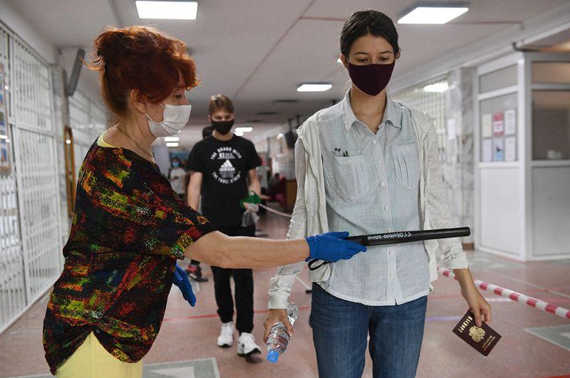 Сотрудница службы безопасности досматривает ученицу на наличие запрещенных на экзамене предметов перед началом единого государственного экзамена по информатике в образовательном центре гимназии No 6 «Горностай» в Новосибирске.