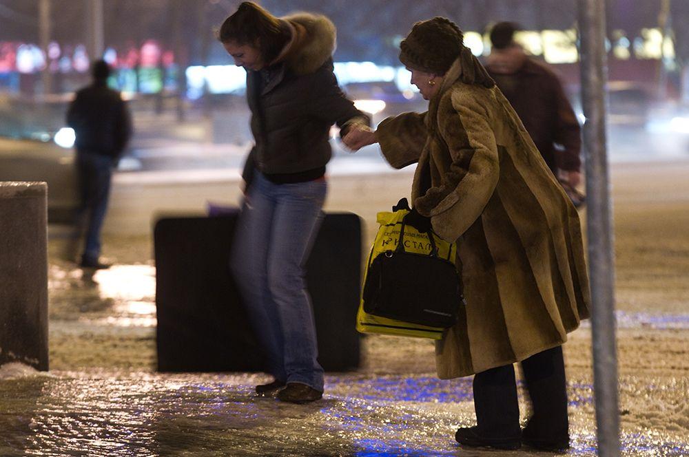 Улицы после прошедшего ледяного дождя превратились в один сплошной каток. На фото: жители Москвы идут по тротуару, покрытому льдом, на Ленинском проспекте.