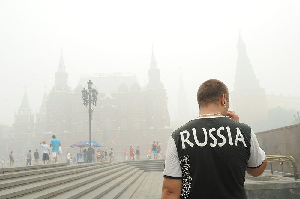 Прохожие на Манежной площади в Москве, окутанной дымом из-за лесных пожаров.