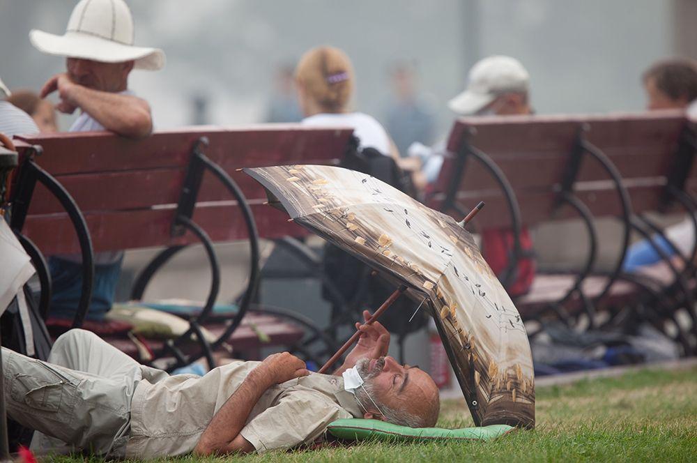Мужчина отдыхает на газоне летом 2010 года.
