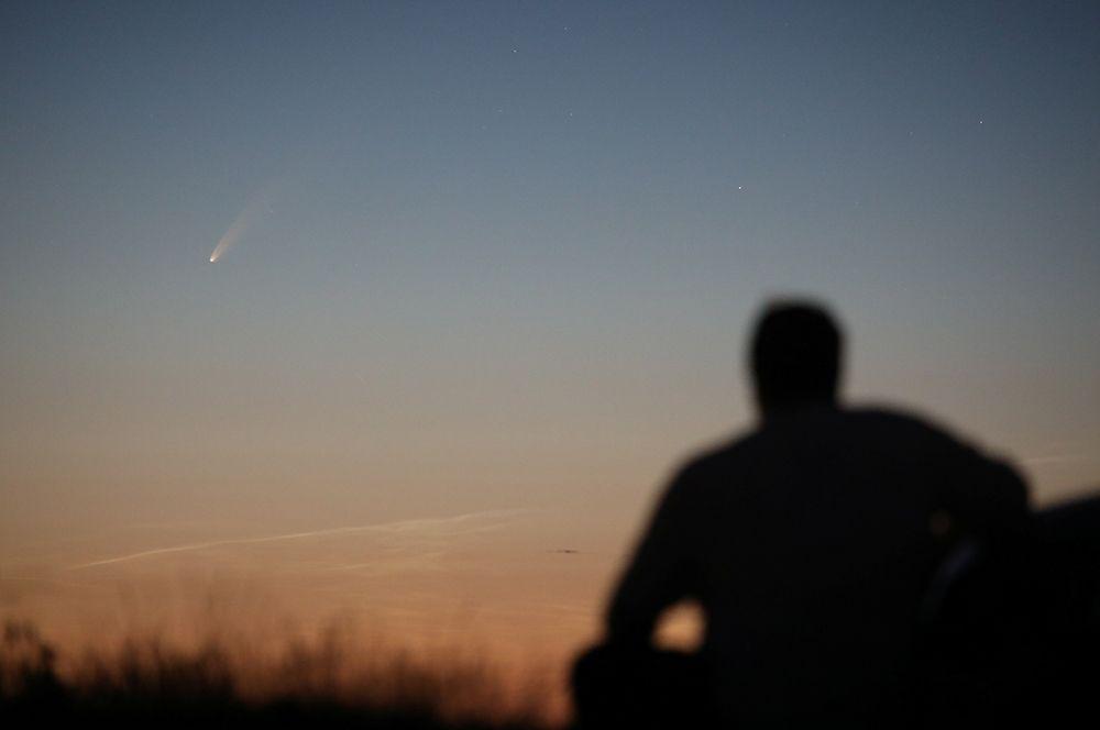 Мужчина наблюдает за кометой в деревне Баллинтой, Великобритания.