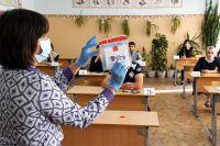 Учительница открывает конверт с диском с заданиями по русскому языку. Село Домна Читинского района Забайкальского края.