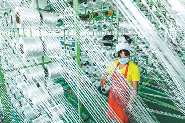 Работница предприятия по производству химического волокна в городе Цзуньхуа, провинция Хэбэй.