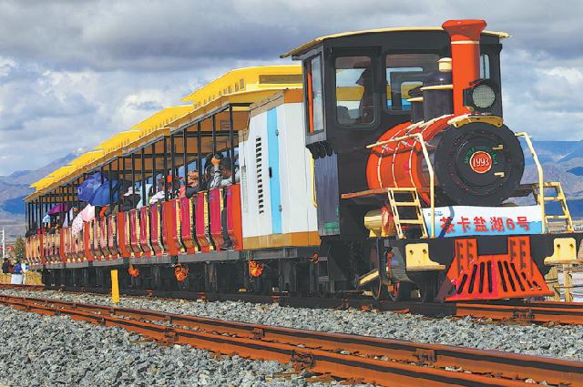 Посетители совершают поездку на поезде, чтобы открыть для себя очарование солёного озера Чака в провинции Цинхай.