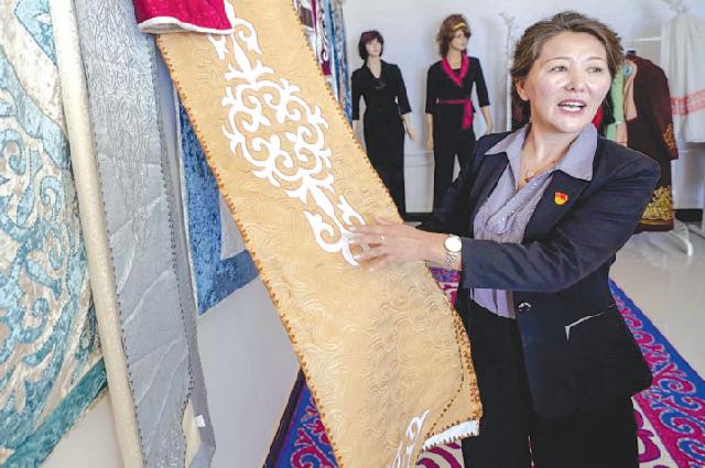 Руководитель мастерской в селе Караой Синьцзян-Уйгурского автономного района Булбул Забуркай знакомит посетителей с традиционной казахской вышивкой.