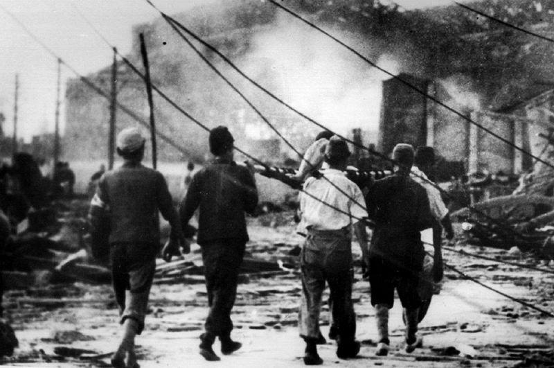 Японцы выносят жертву взрыва из дымящихся руин в Хиросиме, Япония, 6 августа 1945 года.