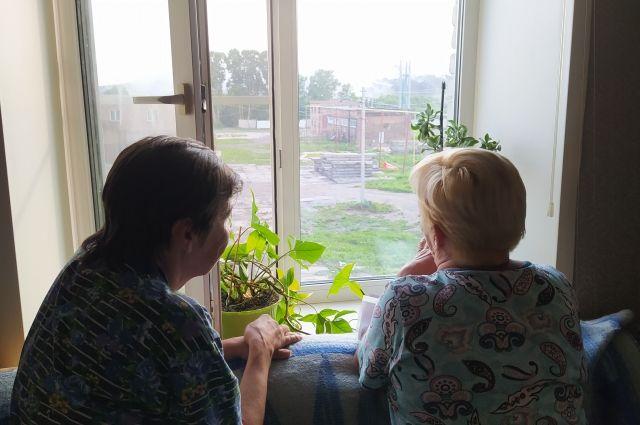 Ирина Кузьмина с соседкой смотрит в окно на горящую свалку.