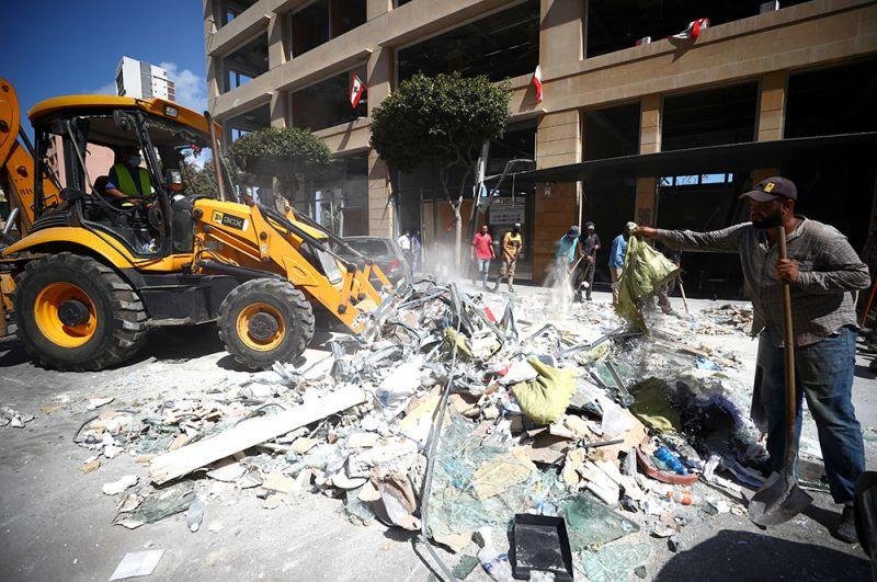 Жители убирают мусор с улиц после взрыва.