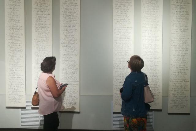Посетители заворожённо рассматривают каллиграфию, напоминающую древние свитки.