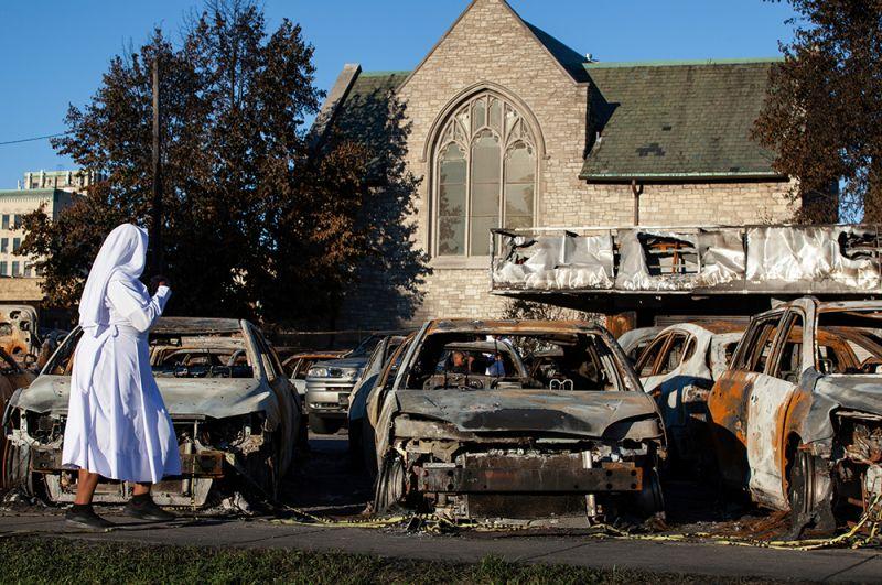 Монахиня проходит мимо автомобилей, сожженных во время протестов против полицейского произвола на одной из улиц города Кеноша в Висконсине.
