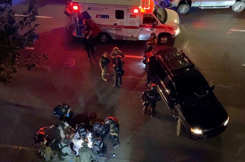 Медики и сотрудники полиции рядом с погибшим во время стрельбы в Портленде.