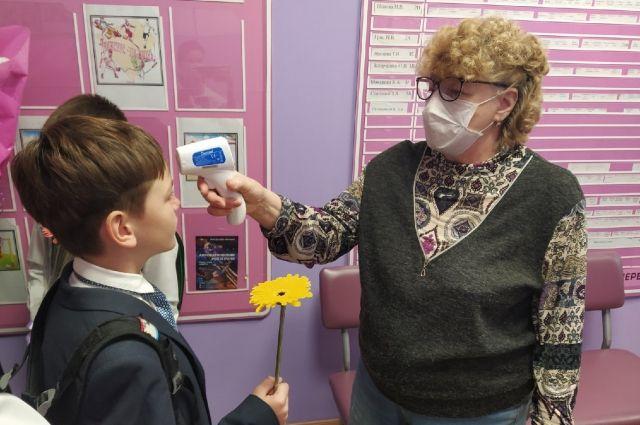 На входе в школу детям измеряют температуру.
