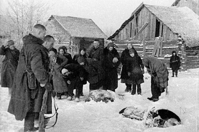 Бойцы Калининского фронта иместные жители осматривают трупы замученных гитлеровцами мирных жителей освобожденной деревни.