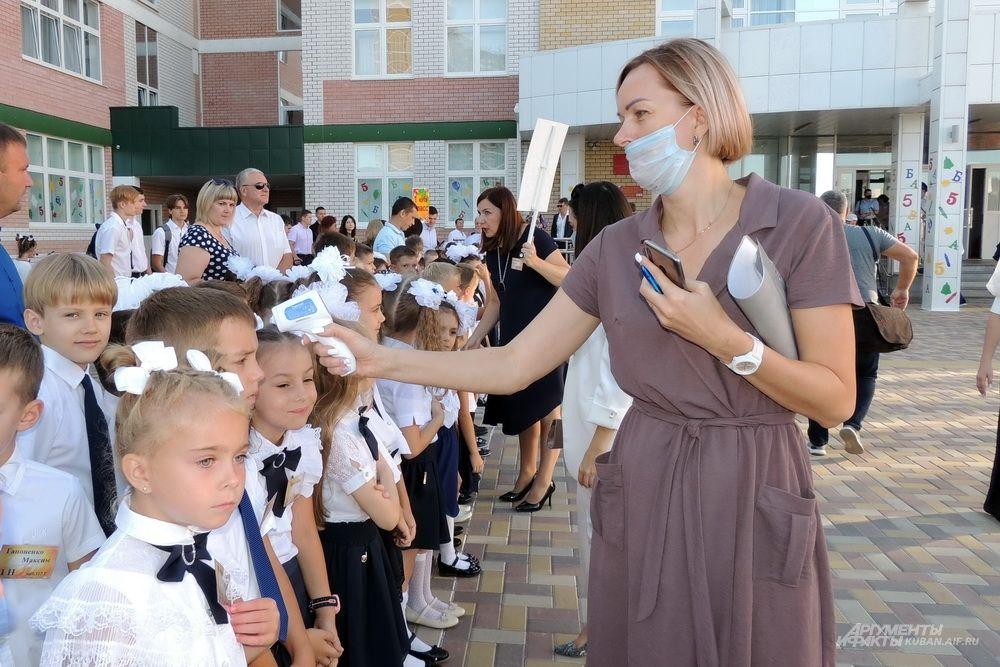 Детям измеряют температуру.