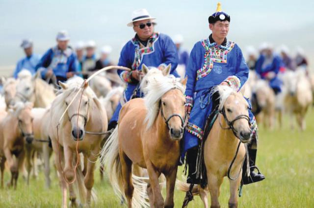 Пастухи скачут на лошадях, чтобы принять участие в народном празднике в автономном районе Внутренняя Монголия.